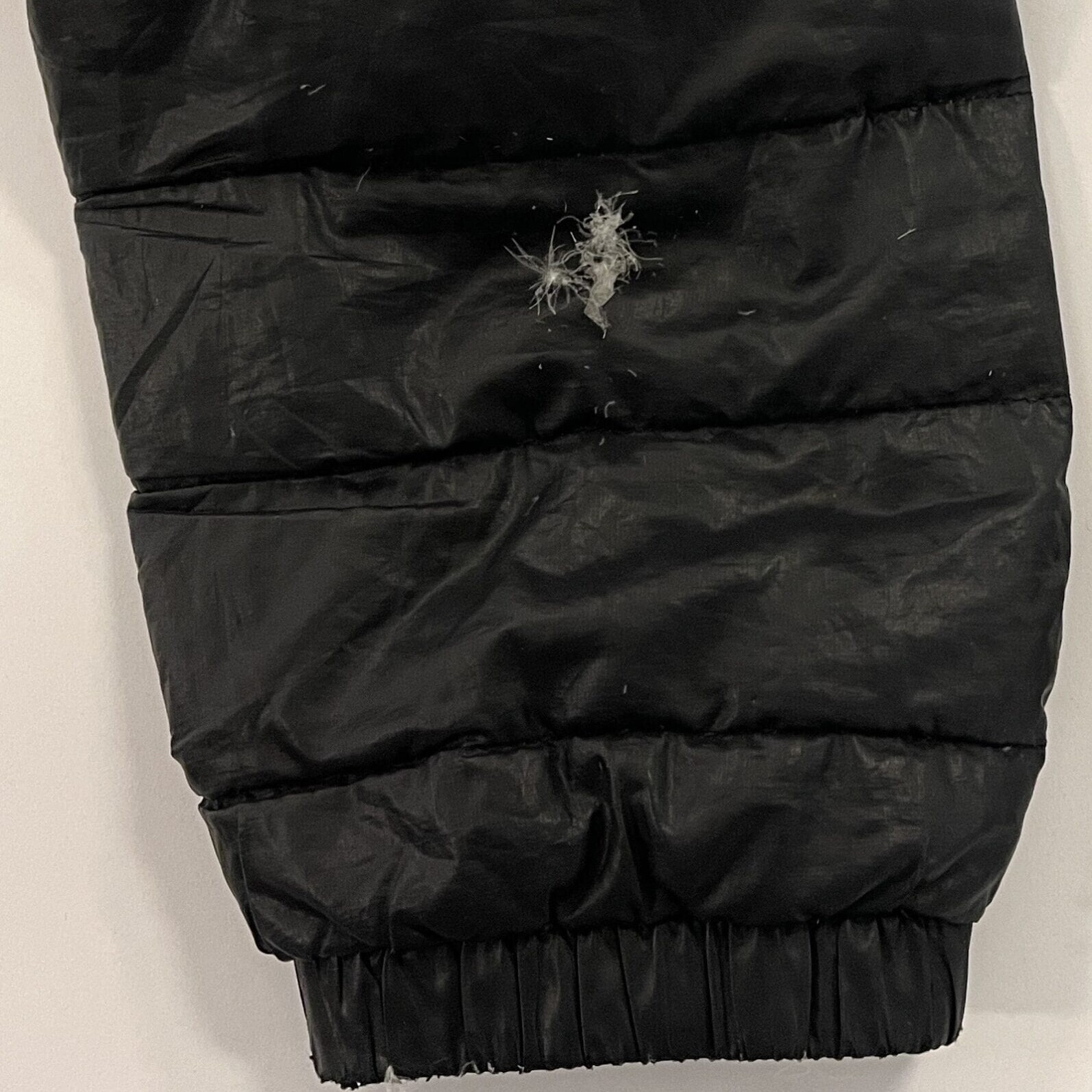 A black puffy jacket sleeve with a hole in it