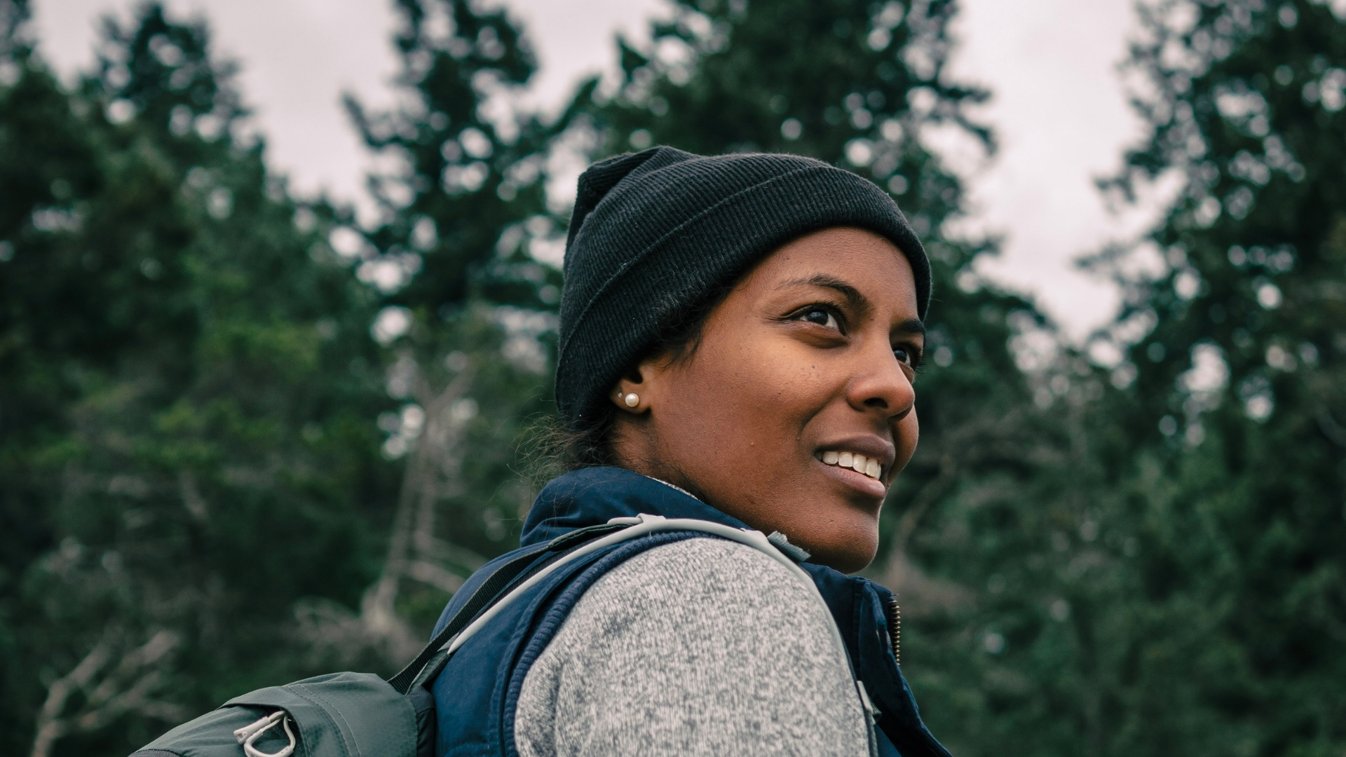 A woman wearing a black beanie and grey shirt out in the forest