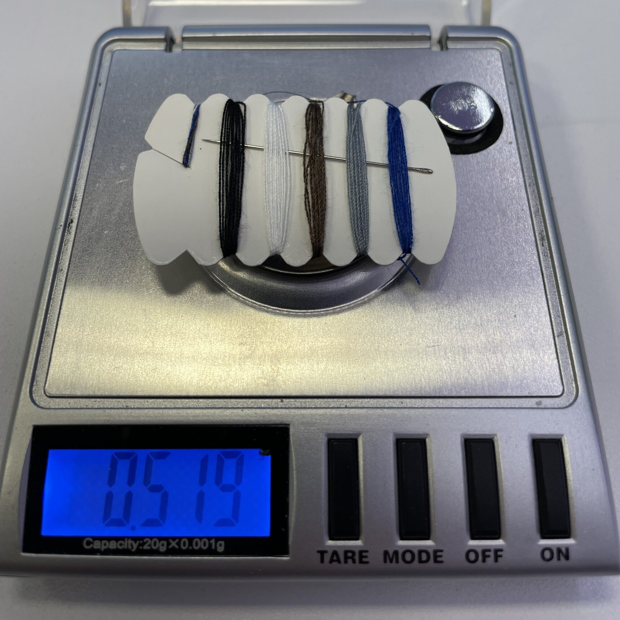 a sewing kit on a scale