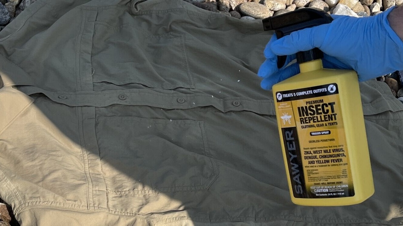 insect repellent being sprayed onto clothing