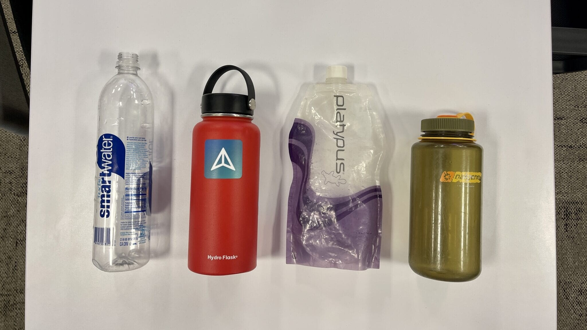 A Smartwater bottle, Hydro Flask, Platypus Water Bag, and Nalgene bottle next to each other on a table.