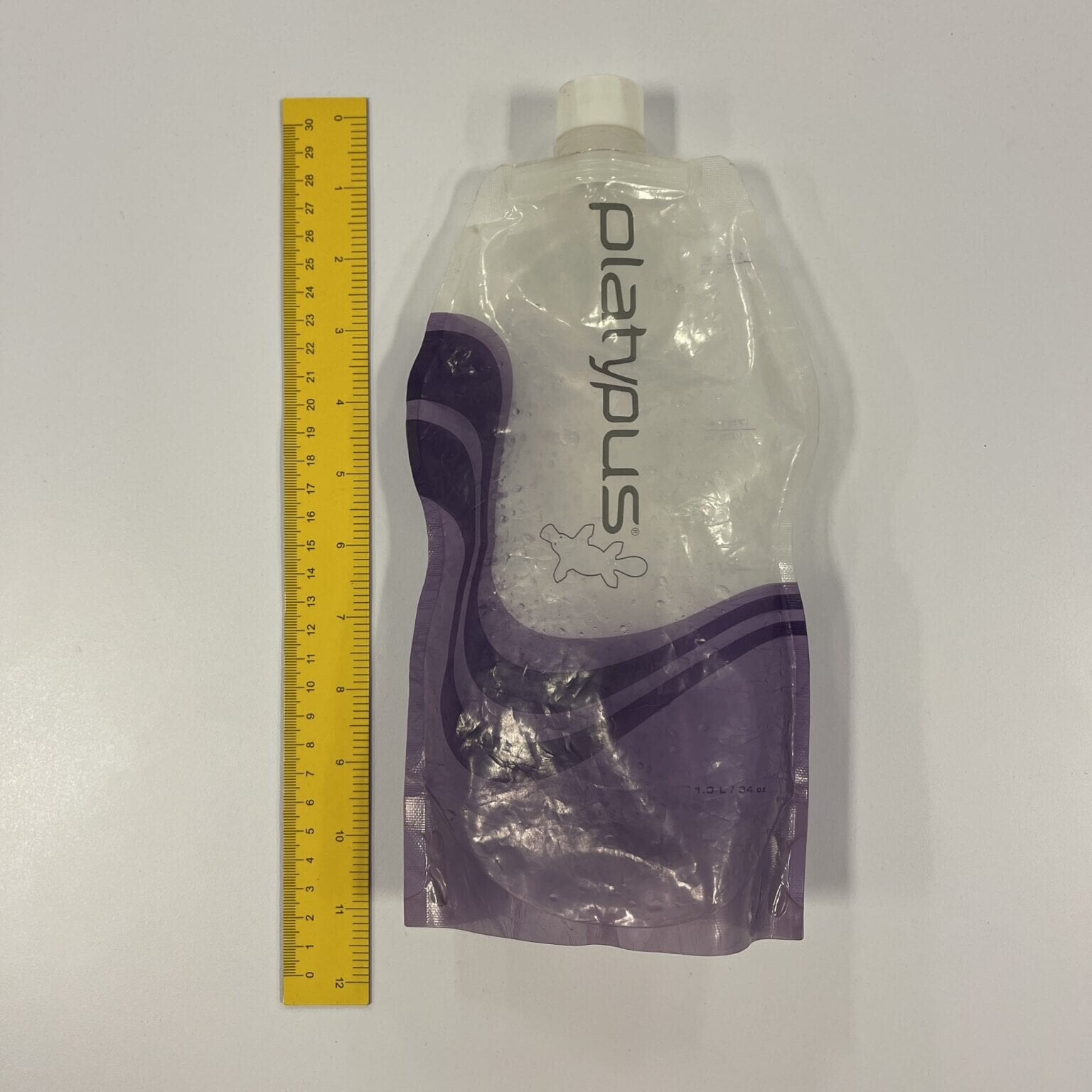 A Platypus water bottle or water bag next to a ruler.