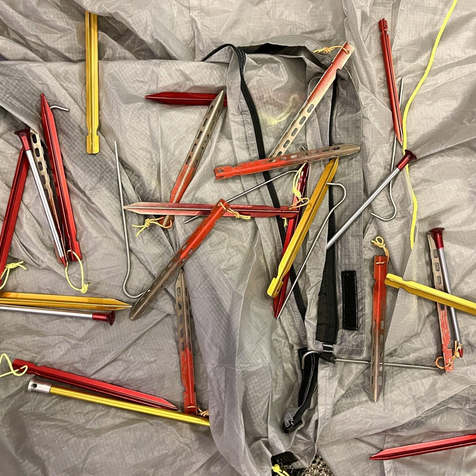 multiple different kinds of tent stakes laid out in a pile