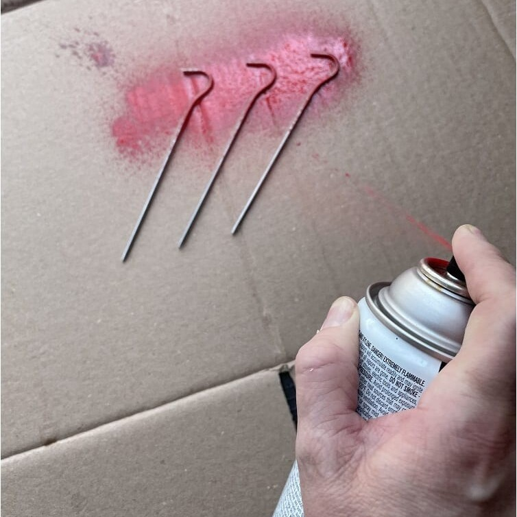 A hand spraying tent stakes over a pice of cardboard with spray paint
