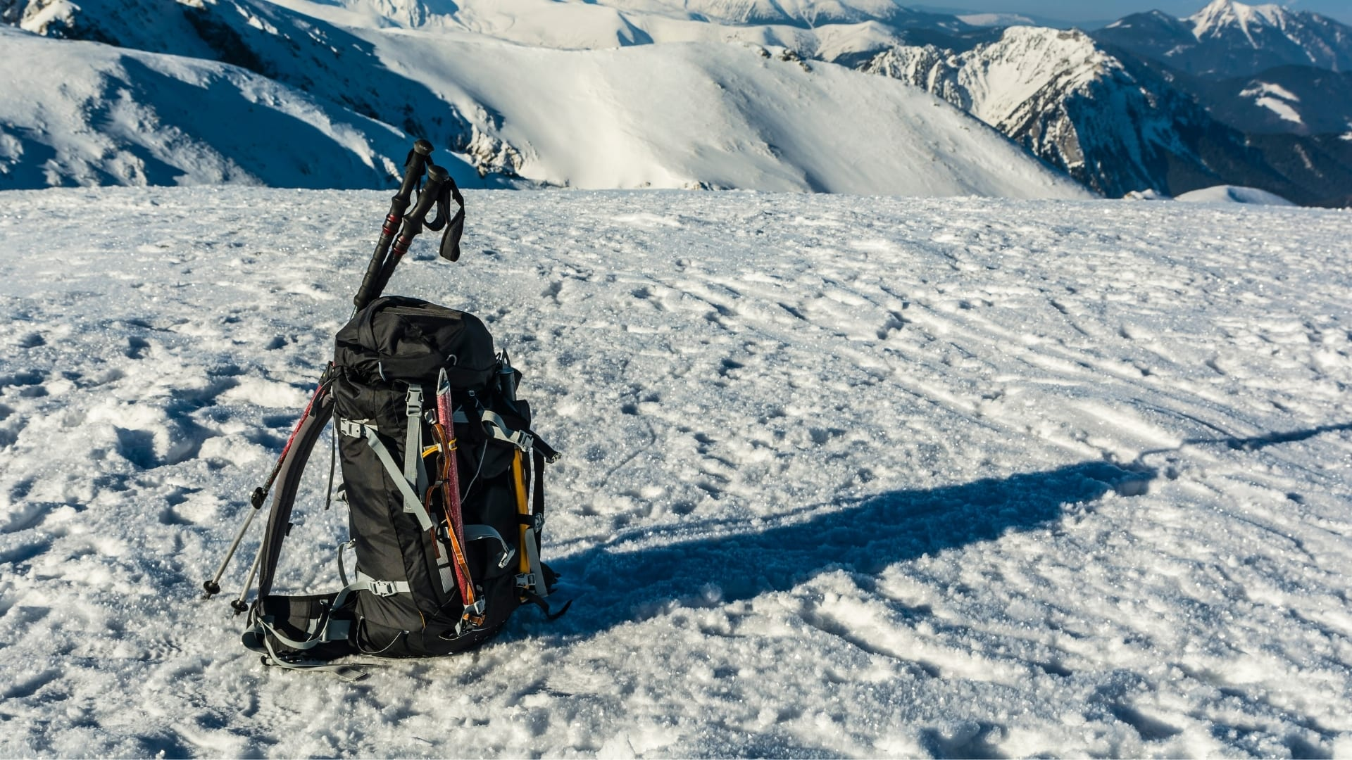 A backpack with an ice axe and hiking poles on the snow