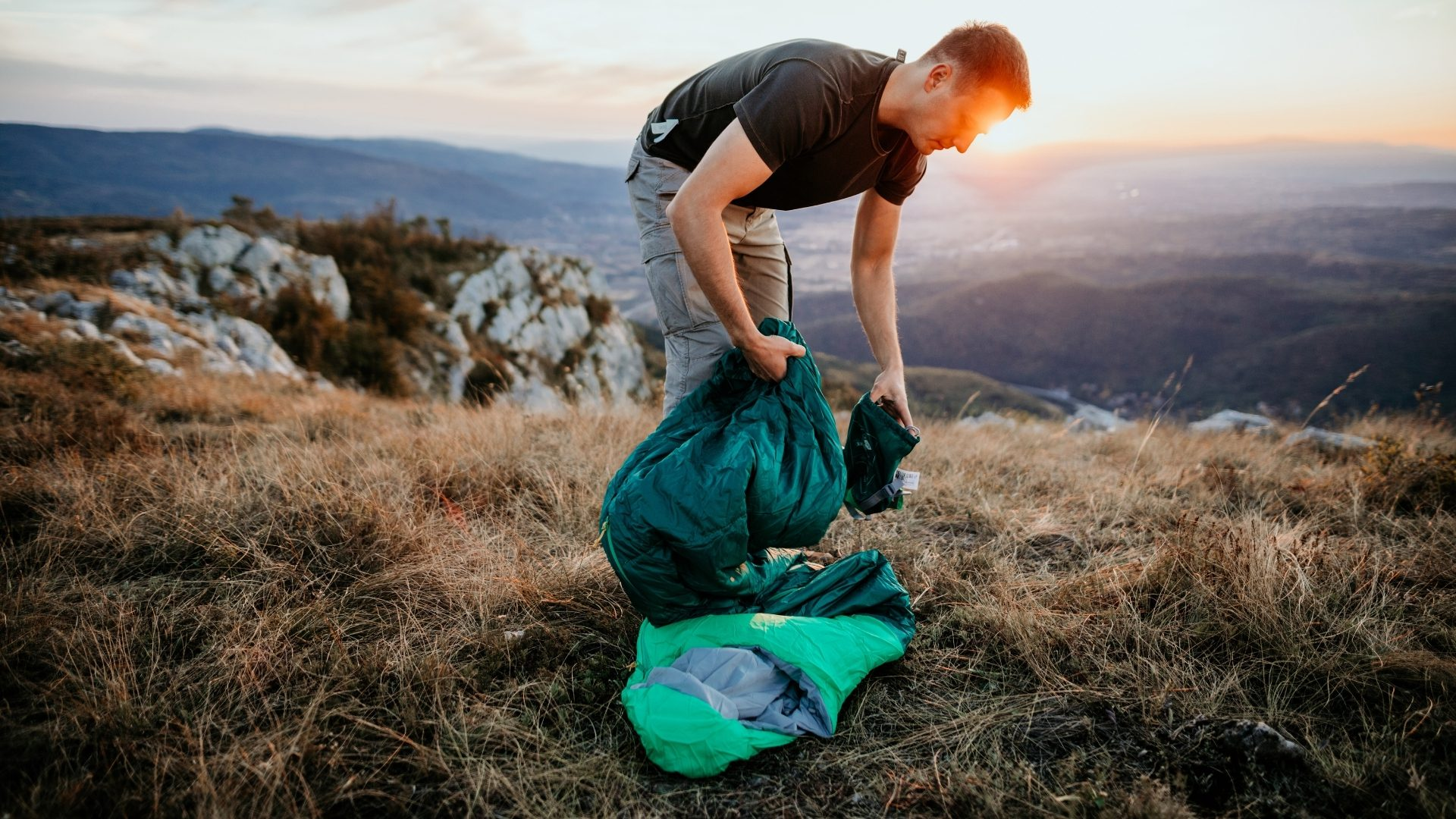 A man packing up a green sleeping bag on a hill side