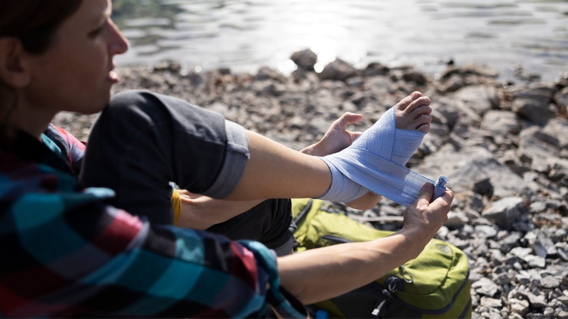 a hiker woman sitting on the ground wrapping her injured foot in a bandage