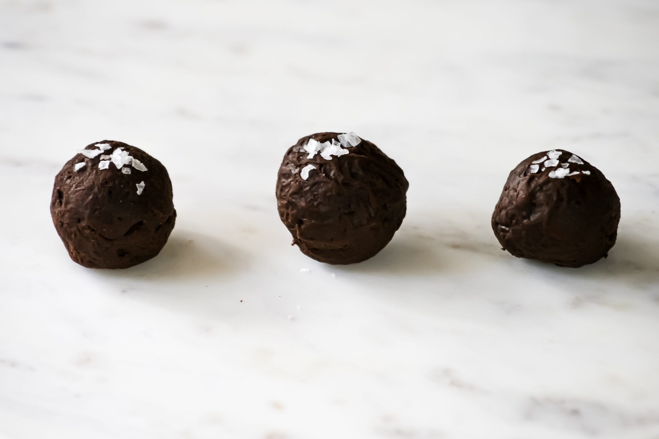 Food photography of dark chocolate truffles with flaked salt