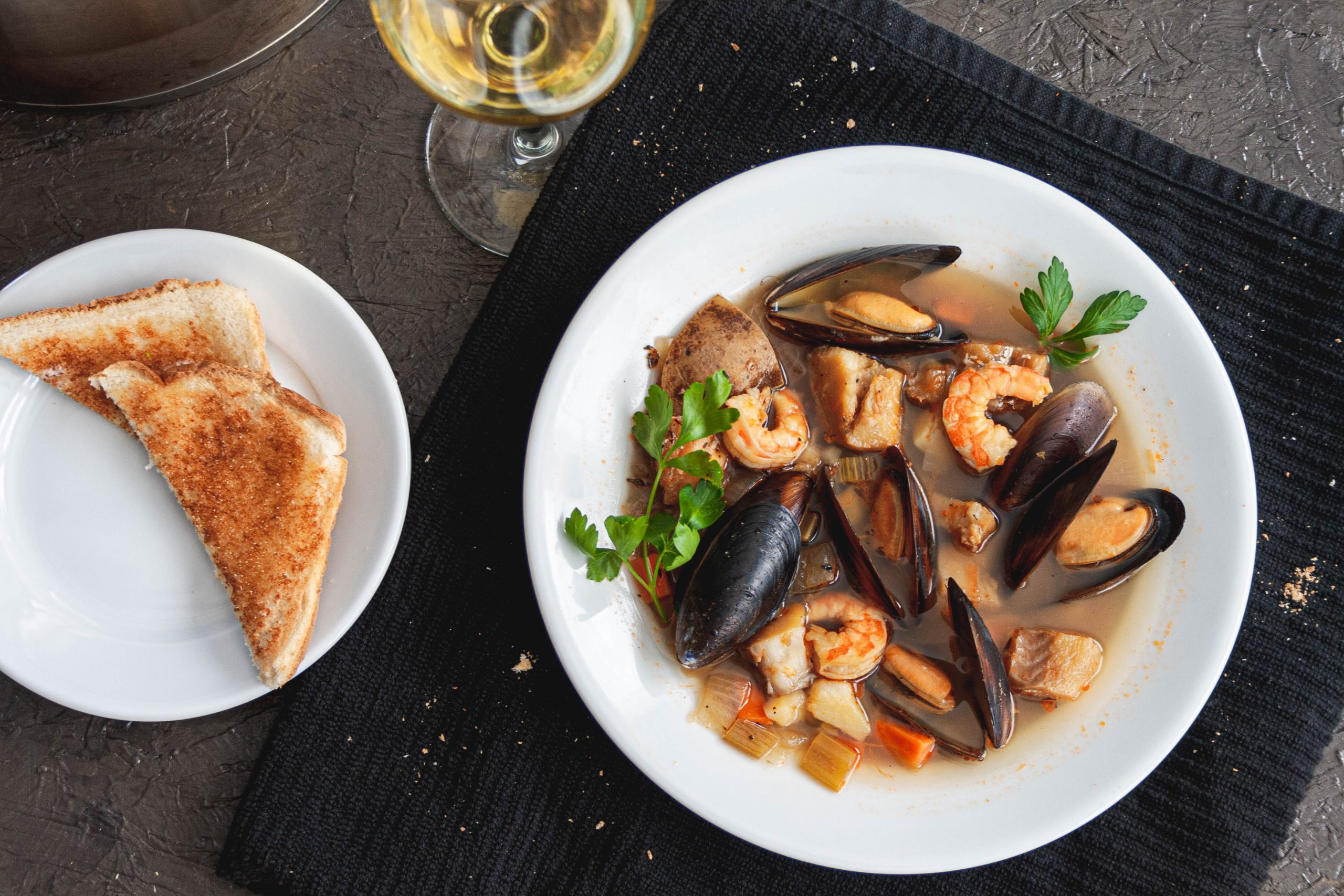 Food photography of seafood stew with wine