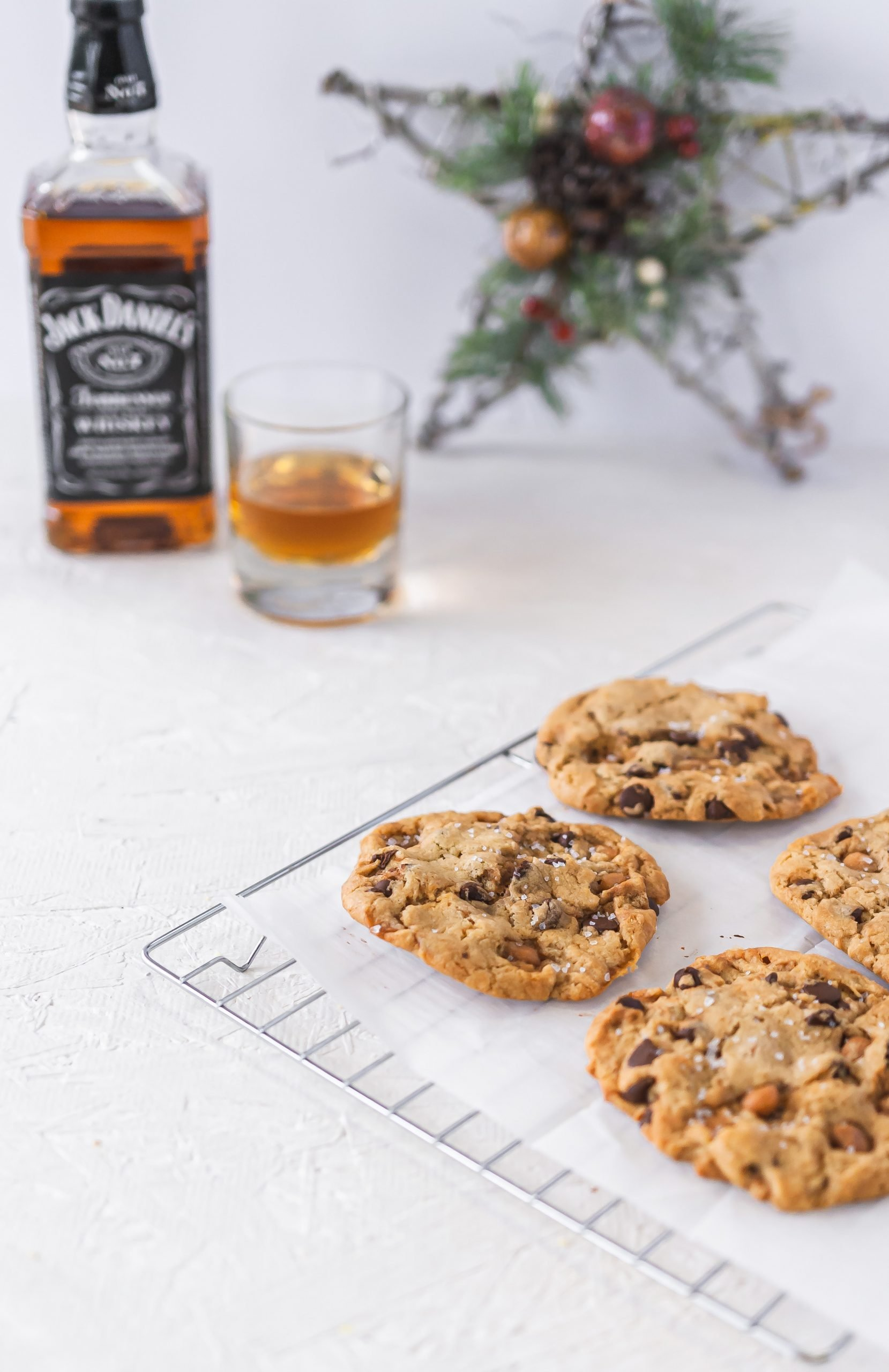 Food photo of sea salt caramel chocolate chip cookies on cooling rack with Jack Daniels