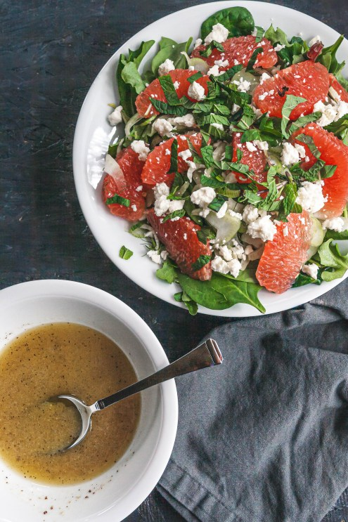 Photo of grapefruit and fennel salad next to a bowl of vinaigrette salad dressing.