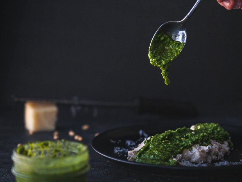 Food photo of arugula pesto being drizzled on chicken