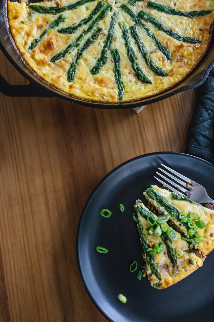 Asparagus onion and ham frittata in skillet next to slices of frittata on plates.