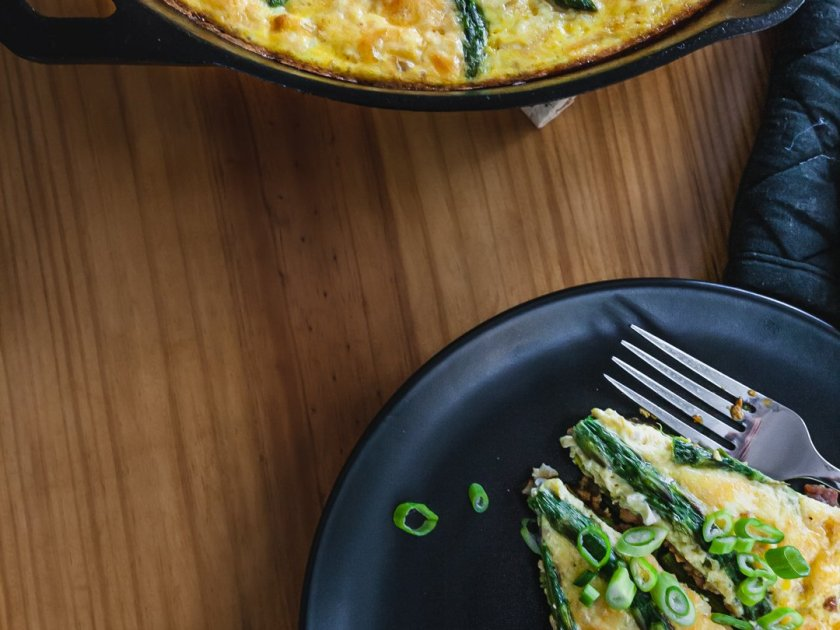 Food photo of asparagus frittata next to plate of sliced frittata.