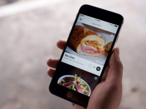 A hand holding a phone with the Uber Eats app open.