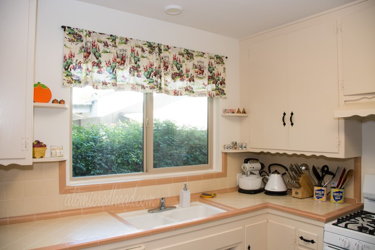 View of the window above the sink in the kitchen, with features a valance of cowboy fabric. Cowboys rest by a fire, some are riding.