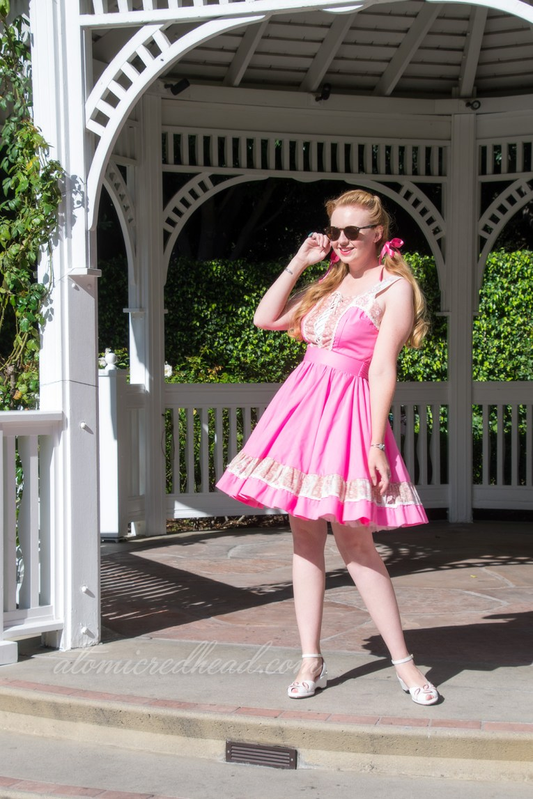 Standing in a gazebo, wearing a pink and white square dancing dress with lace detail.