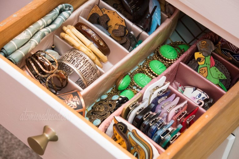 Vintage stocking boxes holding a variety of small jewelry items, including bracelets and brooches
