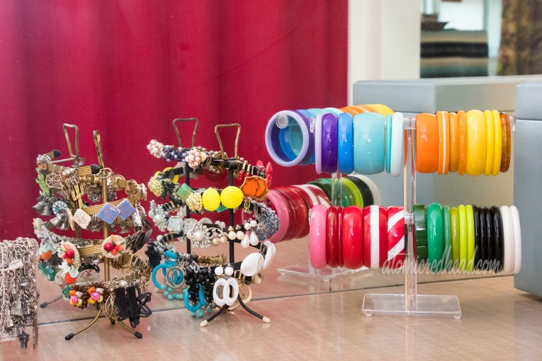 Clip-on and screw back earrings on vintage spinning racks and plastic bracelets on T-rack.