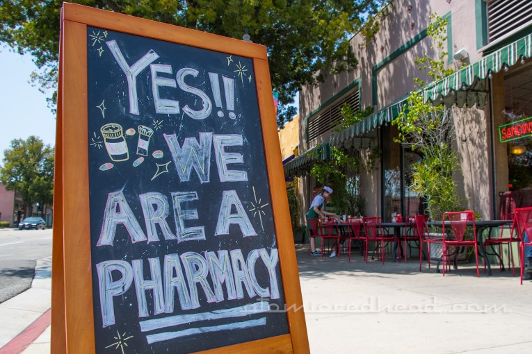 "Sandwich board reading ""Yes!! We are a Pharmacy"""
