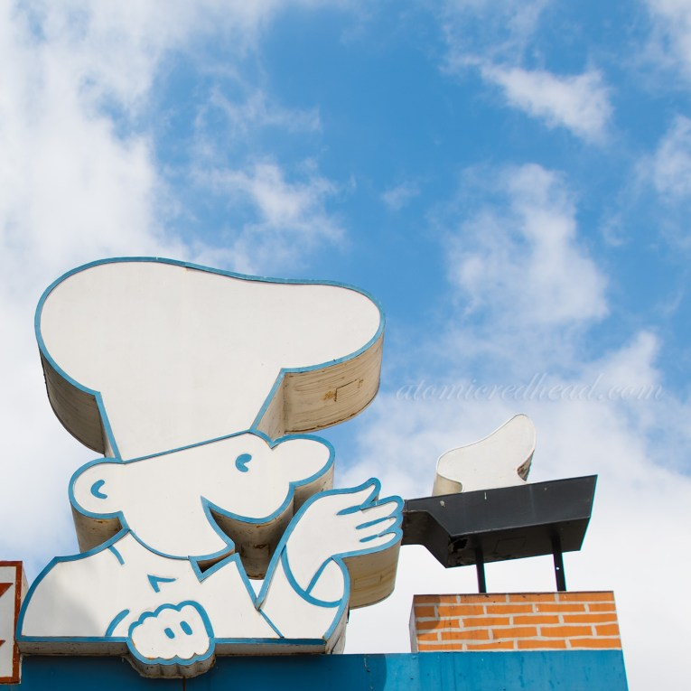 Close up of Original Pancake House sign, of a chef flipping a pancake in a pan.
