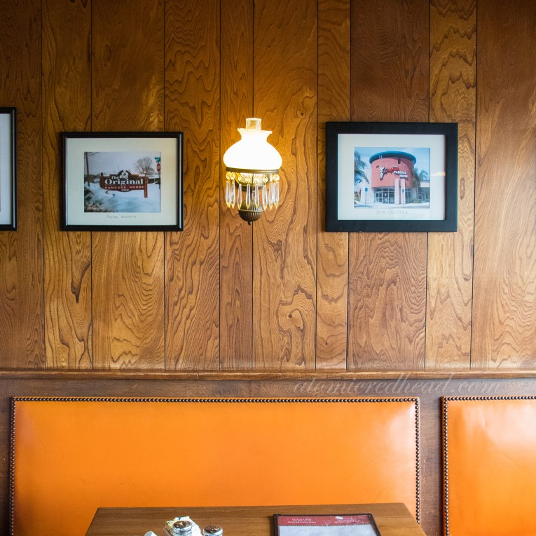 Interior of Original Pancake House, with orange patent leather seats, and colonial revival light fixture and photos of other locations on the wall.