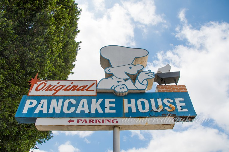 Original Pancake House sign, red, white and blue, with a cartoon version of a chef flipping pancakes.