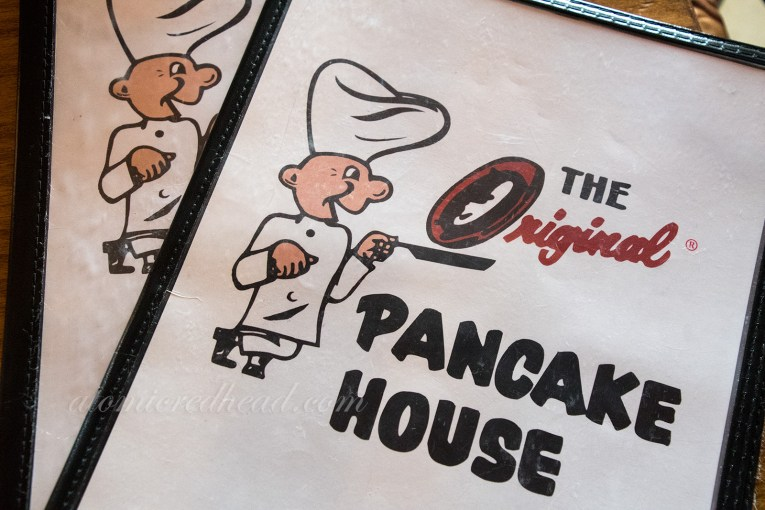 "Menus at The Original Pancake House, feature the same cartoon chef as the sign outside. Here the ""O"" of ""Original"" is the pancake that is being flipped."
