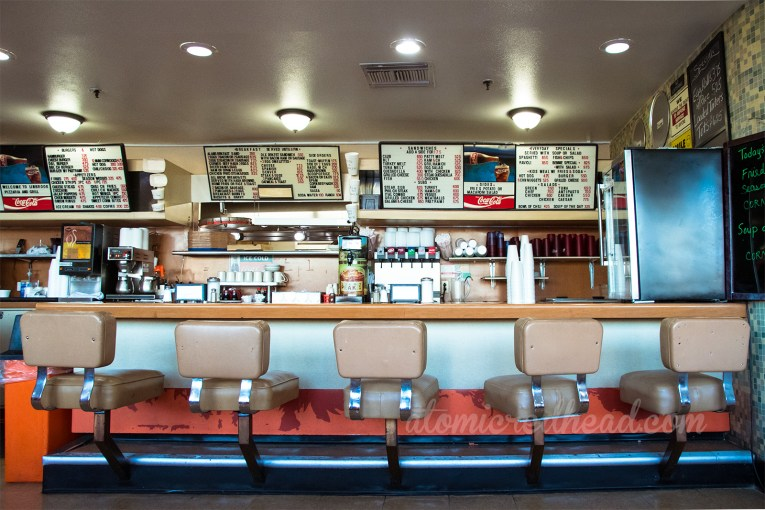 Inside the coffee shop, a menu board hangs above with tan bar stools at the counter.