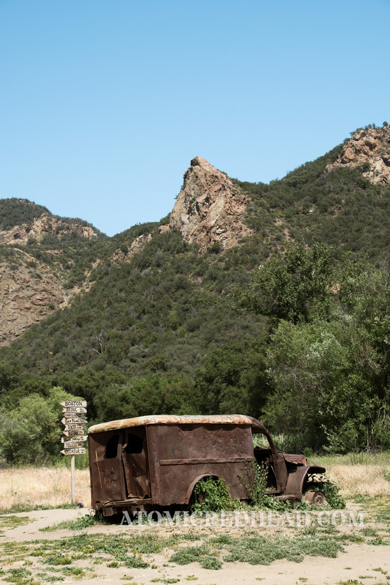 The rusted ambulance sitting in front of the sign post with a high peek in the background, a peek noticeable and seen in the show.