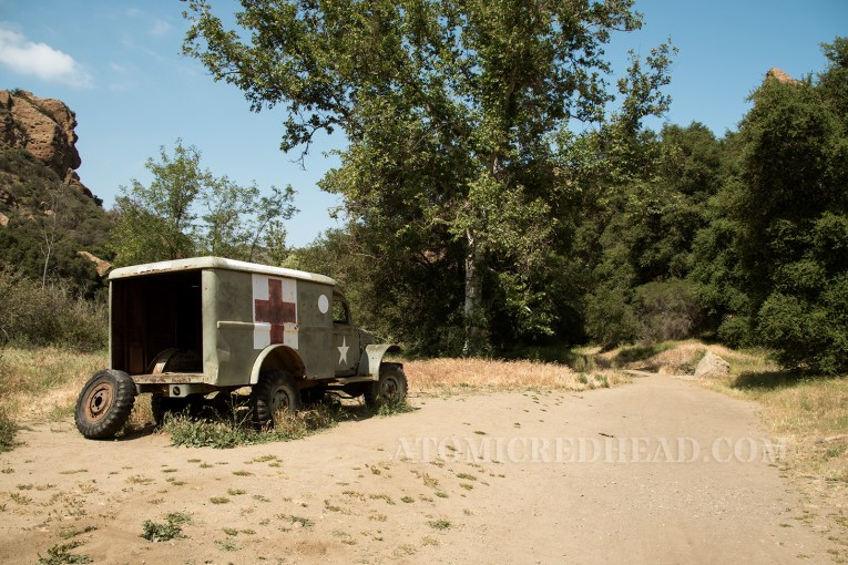 A green ambulance with red and white cross on the side, and large white star on the door.