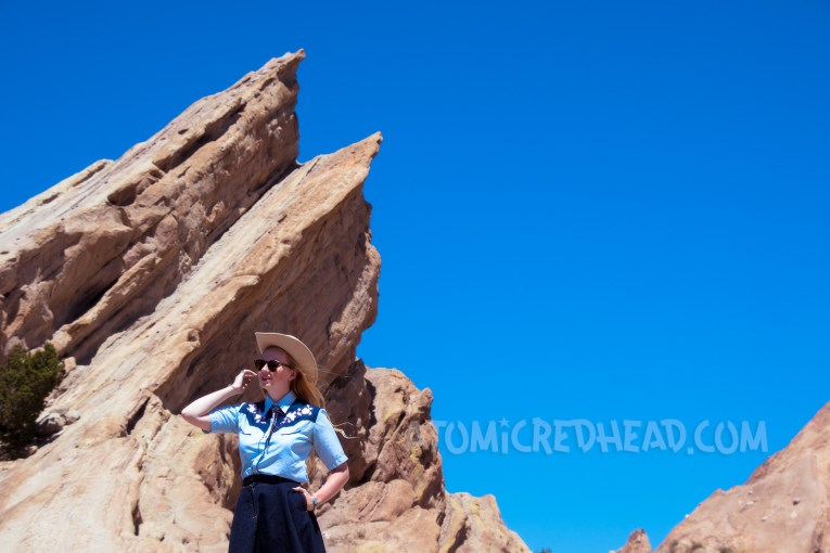 Atop Vasquez Rocks in a denim skirt, two-tone western shirt, UFO bolo tie by Kesha, and a cream western wear hat.