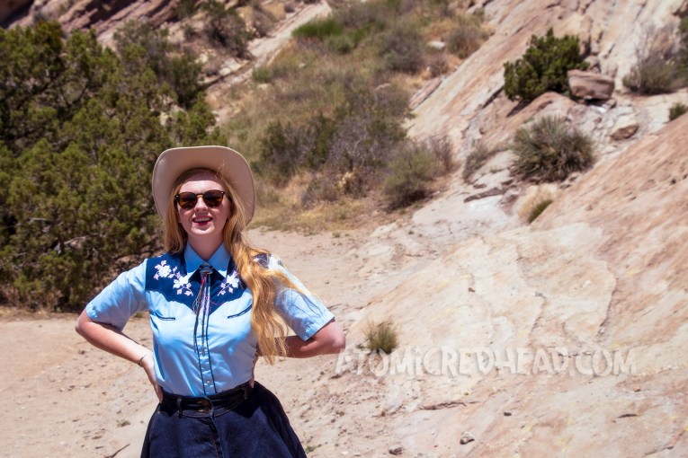 Exploring Vasquez Rocks in a denim skirt, two-tone western shirt, UFO bolo tie by Kesha, and a cream western wear hat.