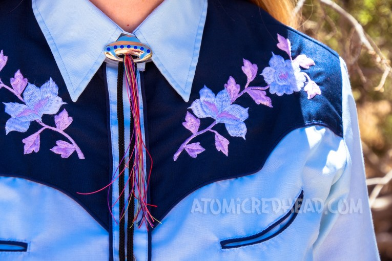 Close-up of the embroidery of my top - pink and white flowers, and a UFO bolo tie.