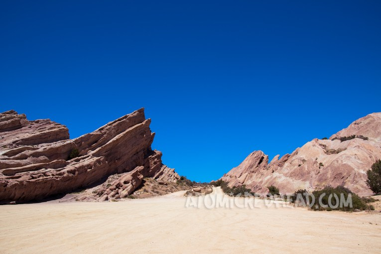Peaks of Vasquez Rocks with a valley to drive between, against a bright blue sky.