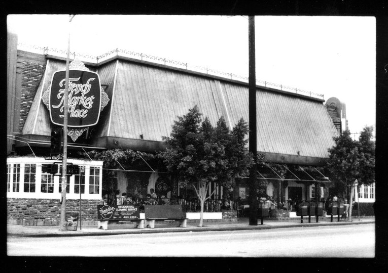 "Vintage black and white photograph of the exterior of The French Market Place. High pitch roof comes down in wrought iron, and a large sign with fancy script reads ""The French Market Place"""