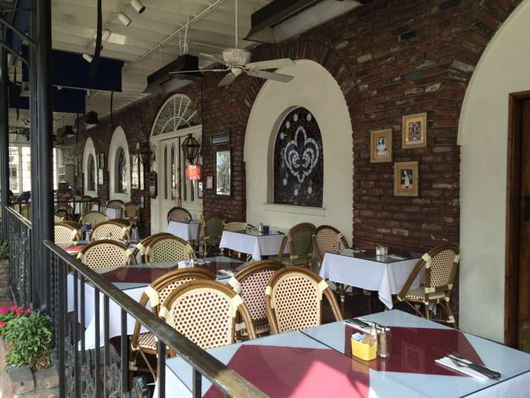 Outside dining of The French Market Place. Exposed brick walls, with fleur de lis stained glass. White linen covered tables with woven chairs. Image from Yelp.