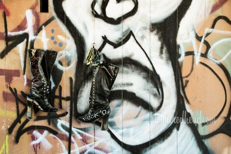 A wall full of graffiti and a pair of tall black boots hang on a nail