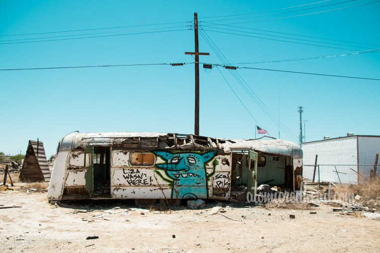 "An abandoned vintage trailer that has suffered a fire, and been tagged. One tag reads ""Liza Wasn't Here"""