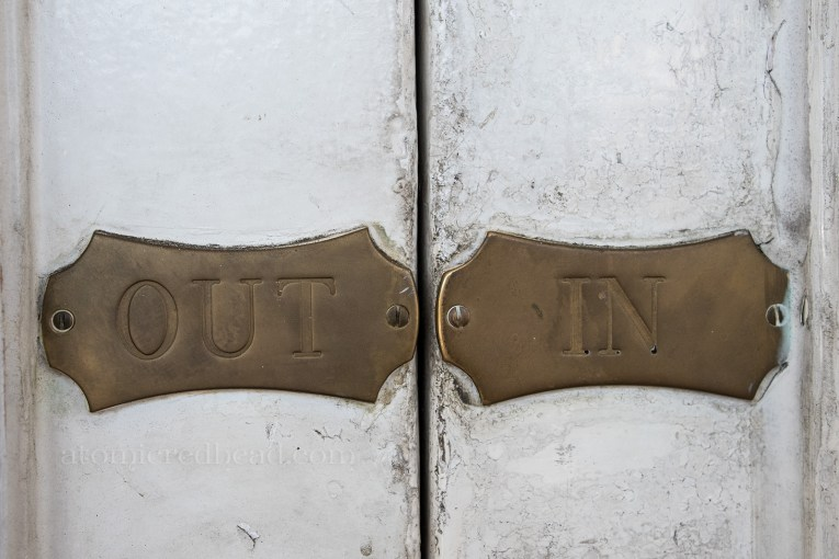 "Close-up of small brass plaques on the front doors reading ""out"" on the left, and ""in"" on the right."