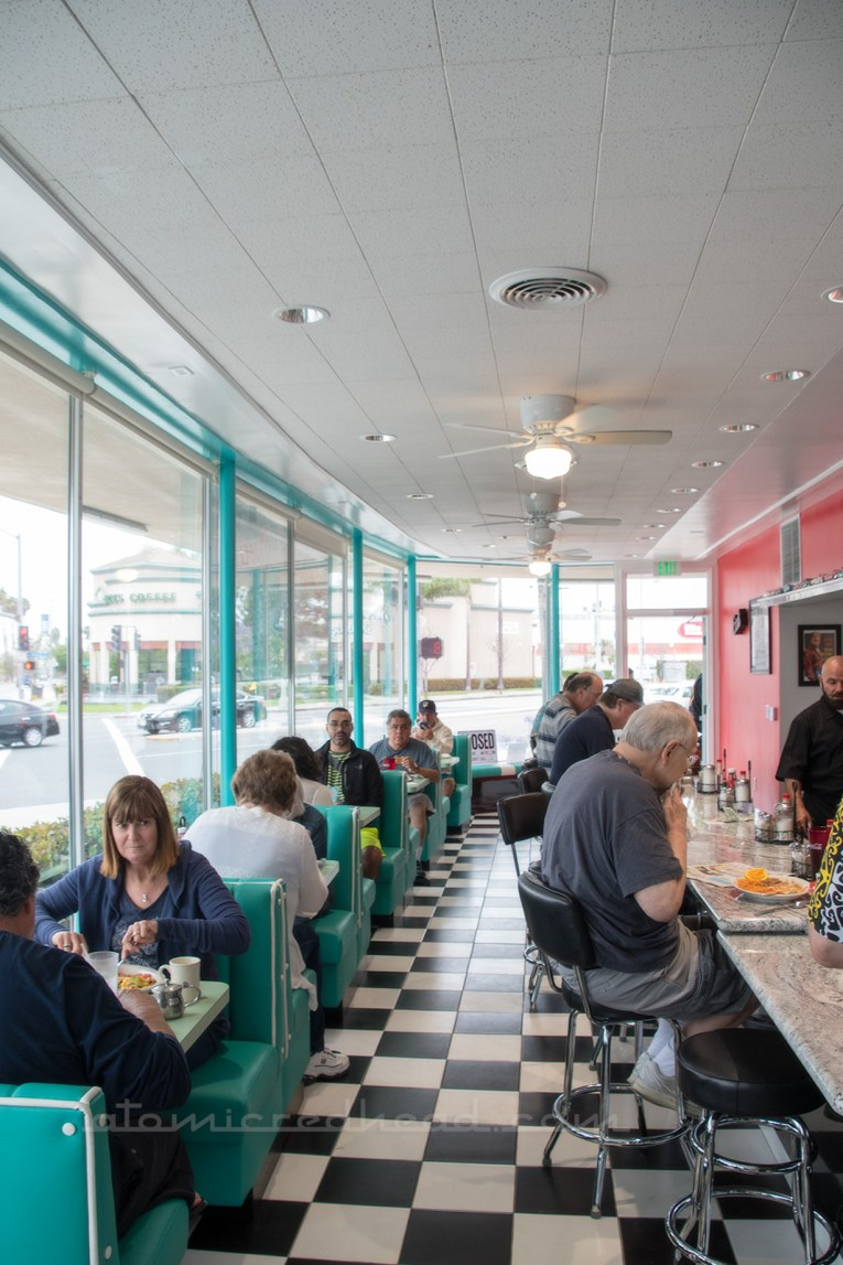Looking down the counter at George's 50s diner. Counter on the right, with small, two seater booths on the left, sit along floor to ceiling and wall to wall windows.