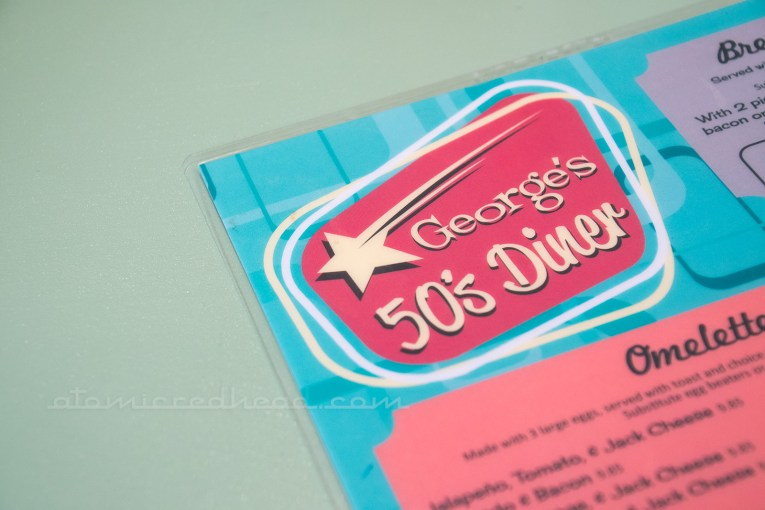 Close up of the new menu, 50s script on a turquoise and pink menu.