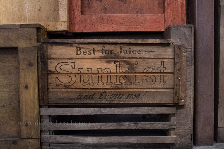 Old crates line a wall, including an old Sunkist crate