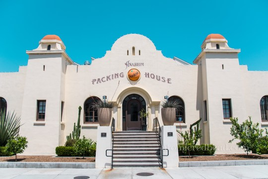 "The Packing House, a mission revival styling building with cream colored stucco and orange color domes. A large orange with ""Sunkist"" across it pops just slightly from the middle above the door."