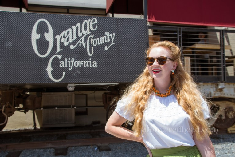 """Old rail cars offer seating for guests, a portion reads """"Orange County, California"""""""