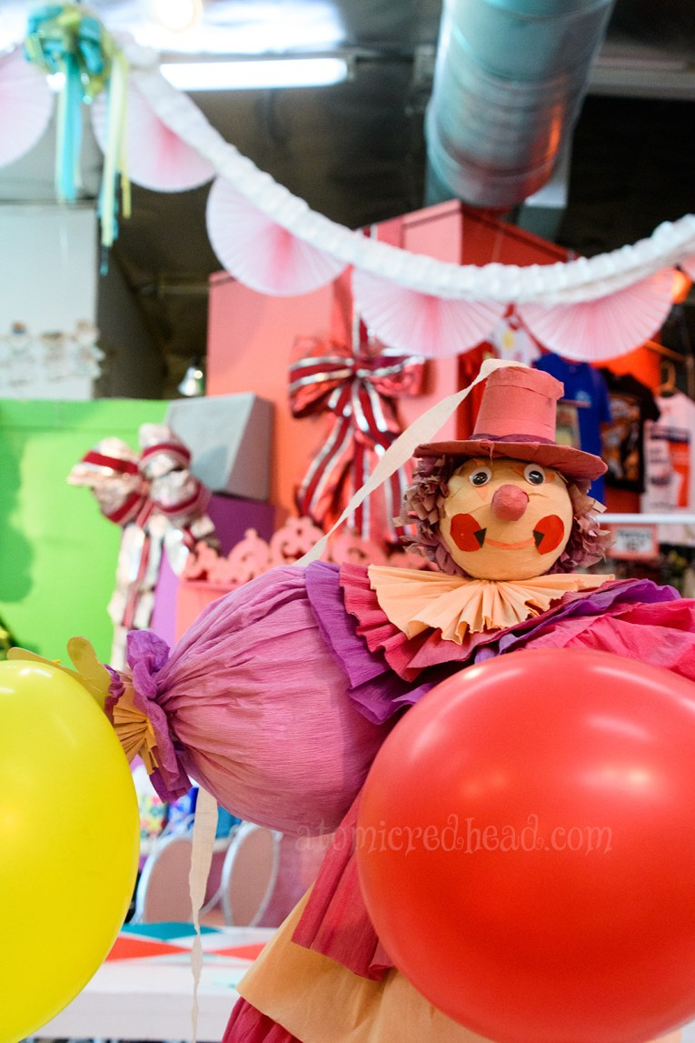 A balloon and papermache clown sits on one of the party tables.