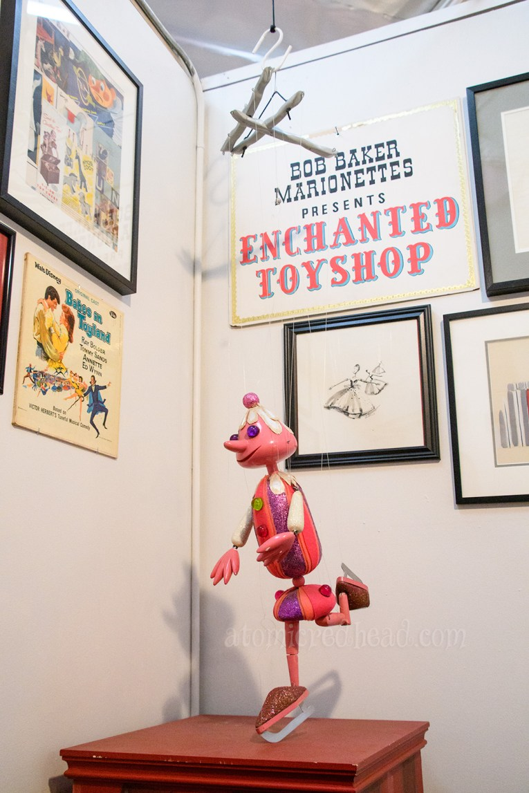 A fanciful pink clown marionette on ice skates hangs near the door.