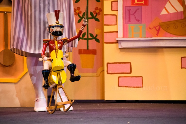 A wooden soldier marionette rides a rocking horse.