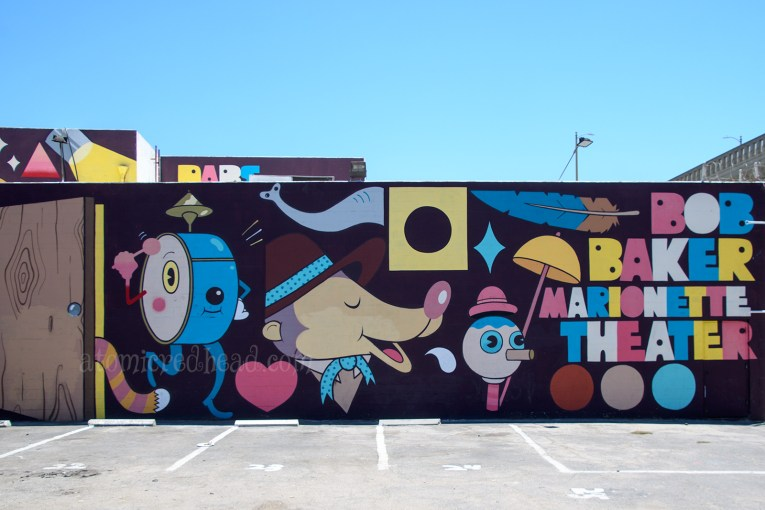 The mural outside of the theater, featuring a large drum that plays itself, a bear, and other quirky shapes.