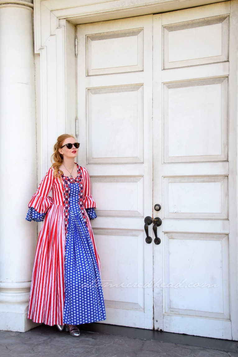 Standing in front of Independence Hall, a large brick and white building, wearing a dress made of red and white stripe fabric and blue with white star fabric, done in the 18th century style.